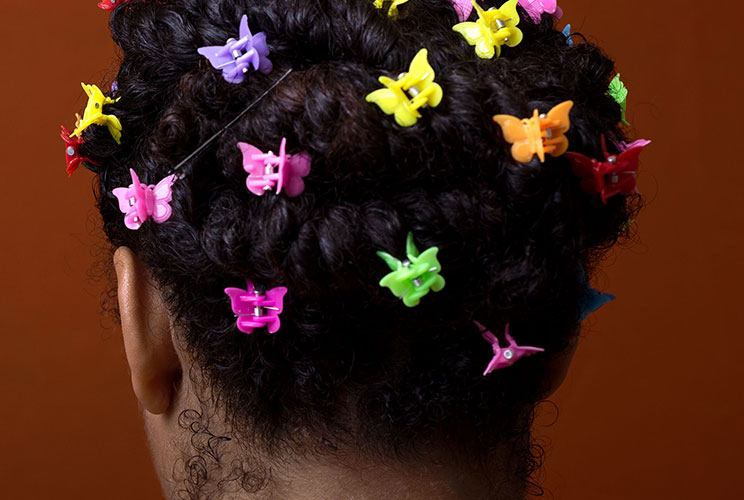 A portrait of the back of someone's head, their hair filled up with different colored butterfly clips.