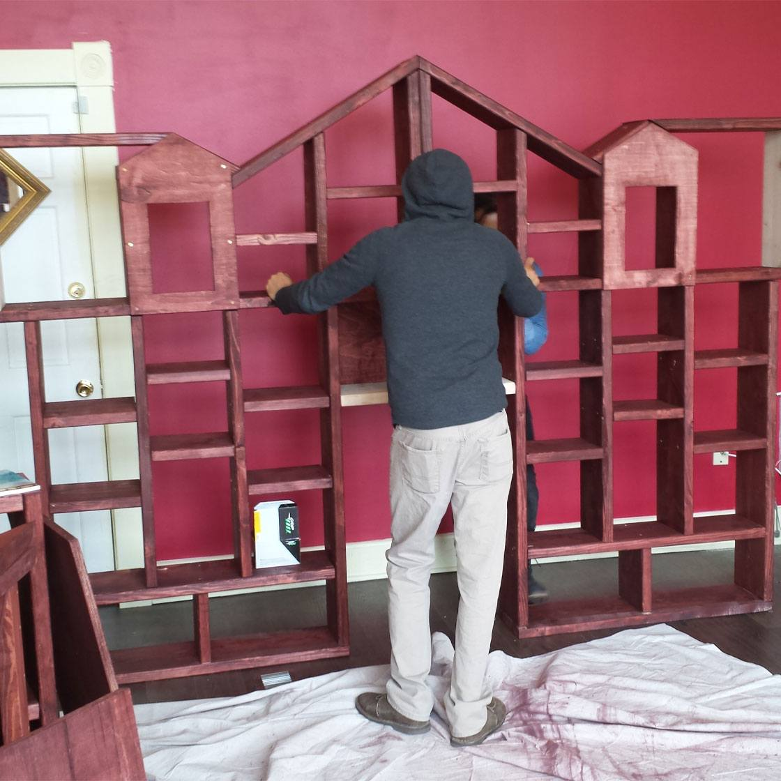 Someone building a decorative bookshelf