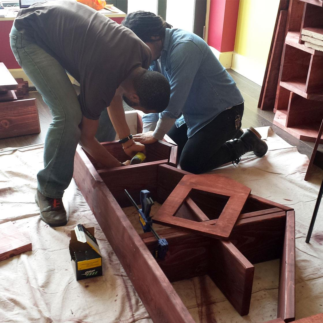 Several people building a bookshelf