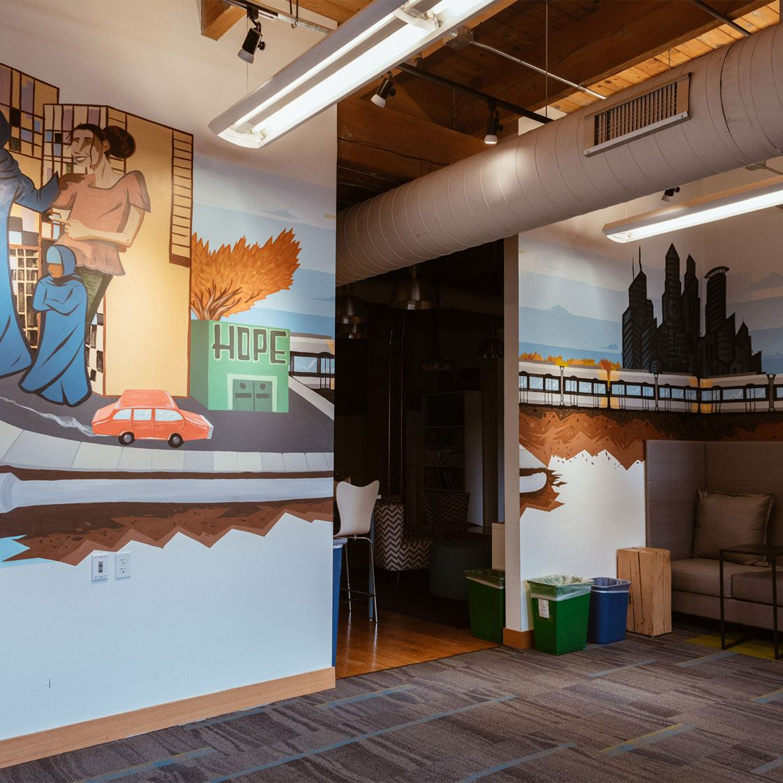 An office space decorated with a painted mural of a cityscape