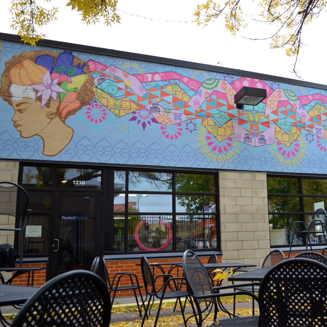 A restaurant patio decorated by a large-scale colorful mural of a woman with long flowing colorful hair