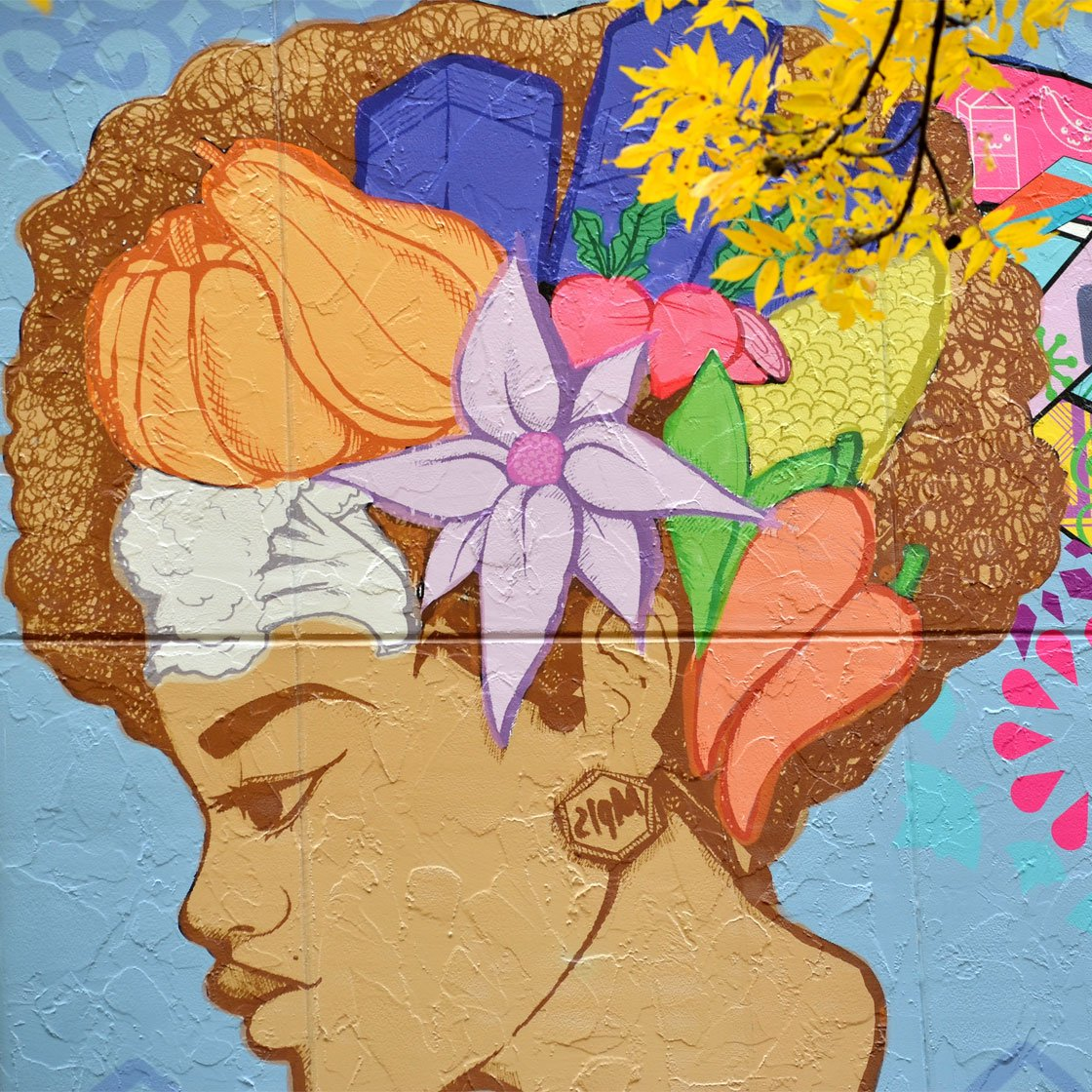 Detail of a large-scale colorful mural of a woman with long flowing colorful hair