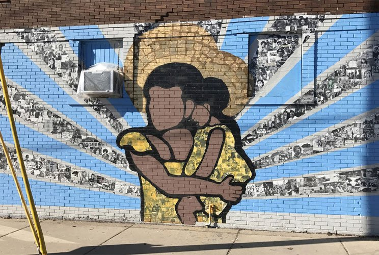 Outdoor large-scale mural of a woman holding a child with rays radiating from them