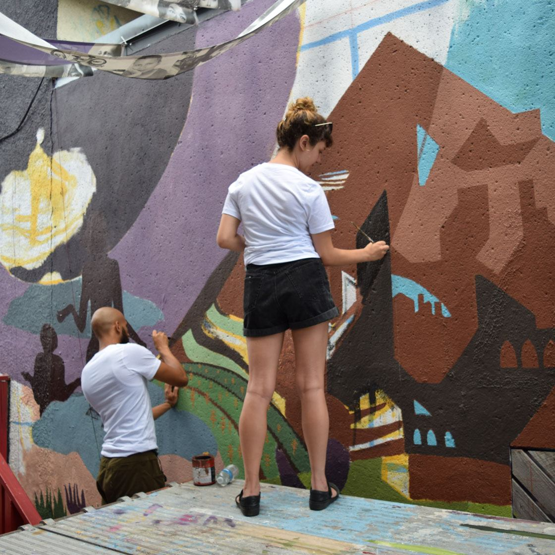 A young person painting a large-scale outdoor mural