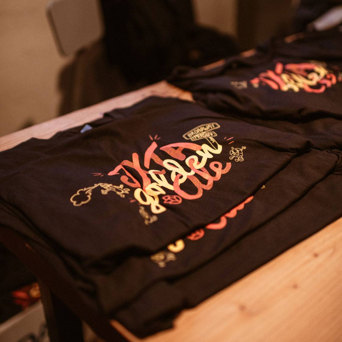 Decorative screen printed shirts with a decorative design with the words JXTA golden ale
