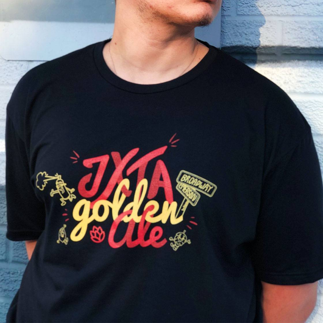 Someone posing wearing a t shirt with a graphically illustrated logo JXTA Golden Ale