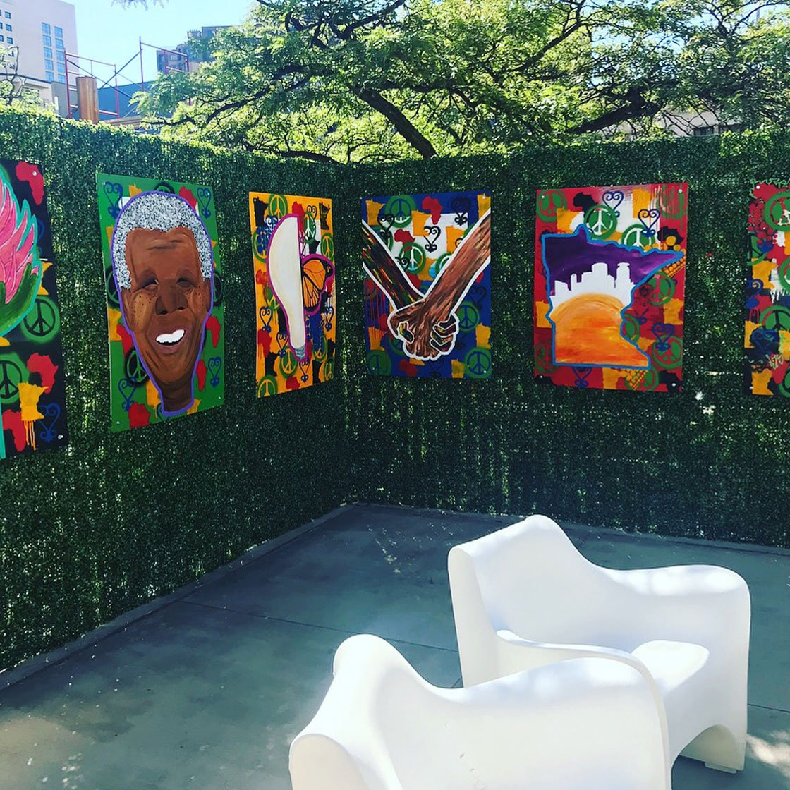 An outdoor patio decorated with vibrant hanging paintings