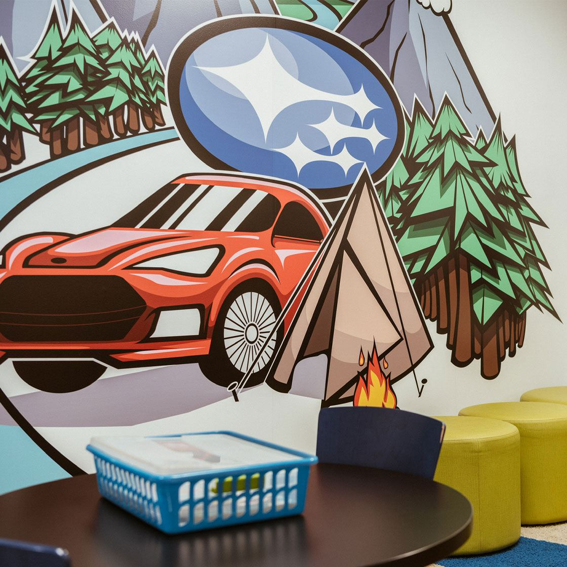 A kids playroom with a graphically illustrated vinyl mural