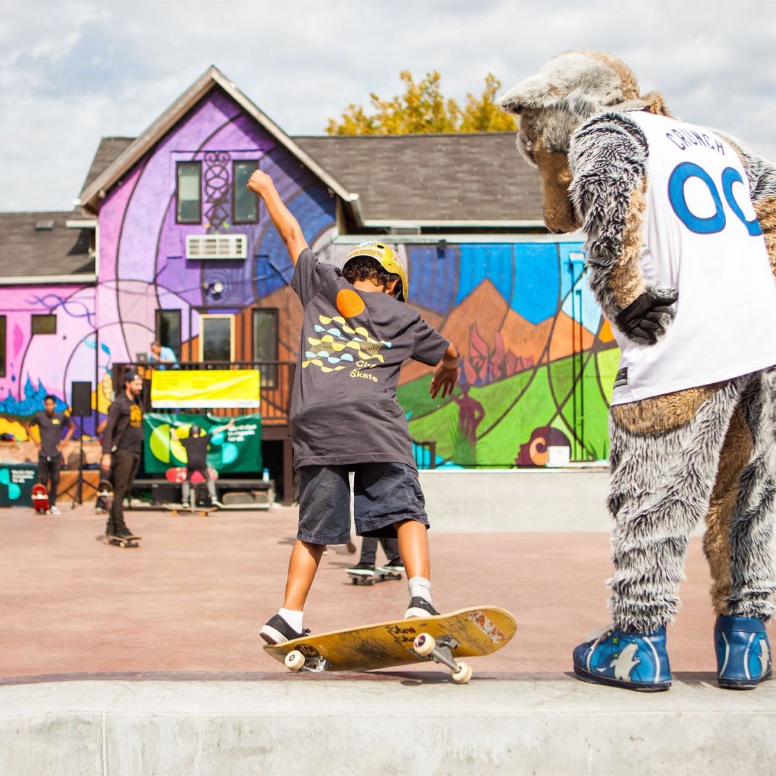 A young person skateboarding with a sports mascot