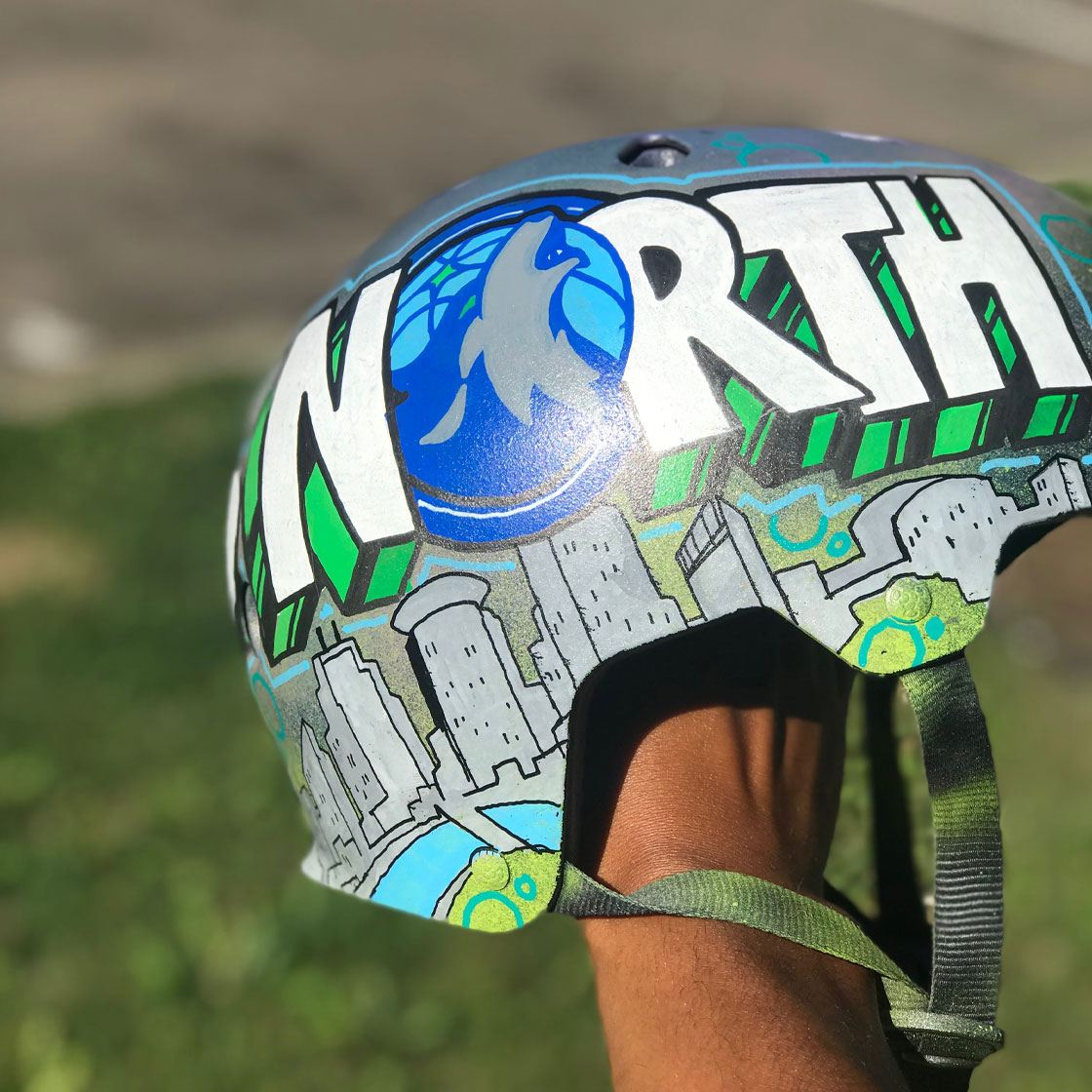 Someone holding a skateboarding helmet decorated with the words All Eyes North
