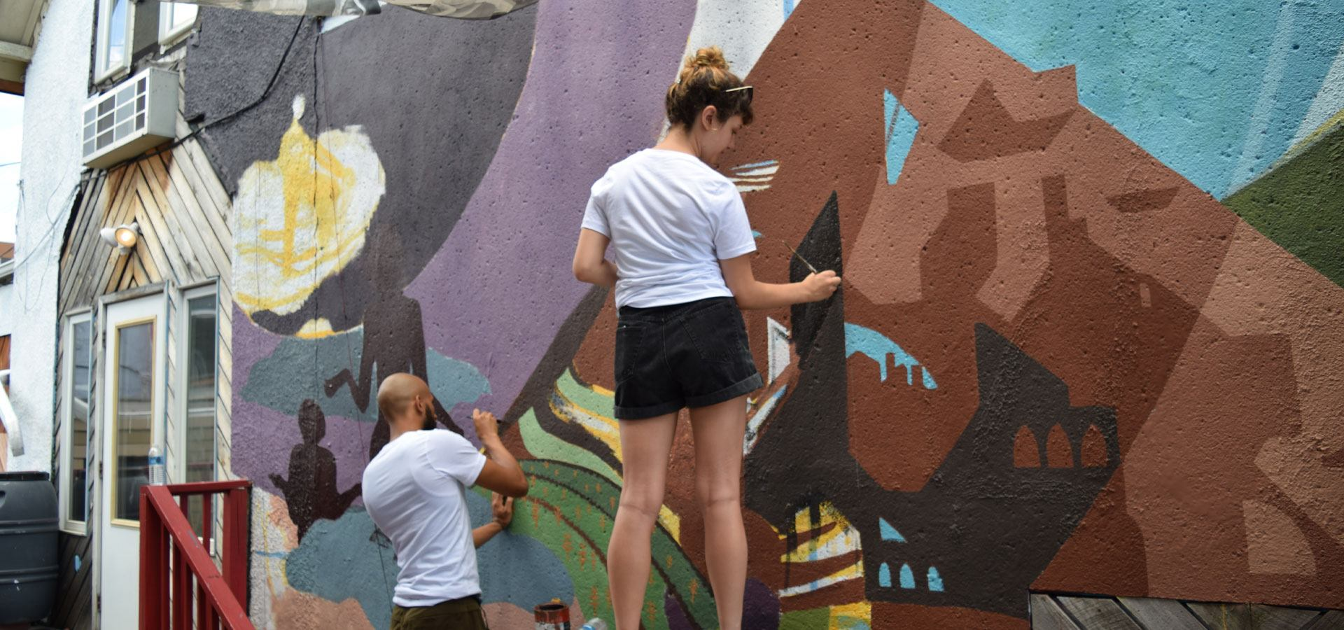 A young person painting a large scale mural