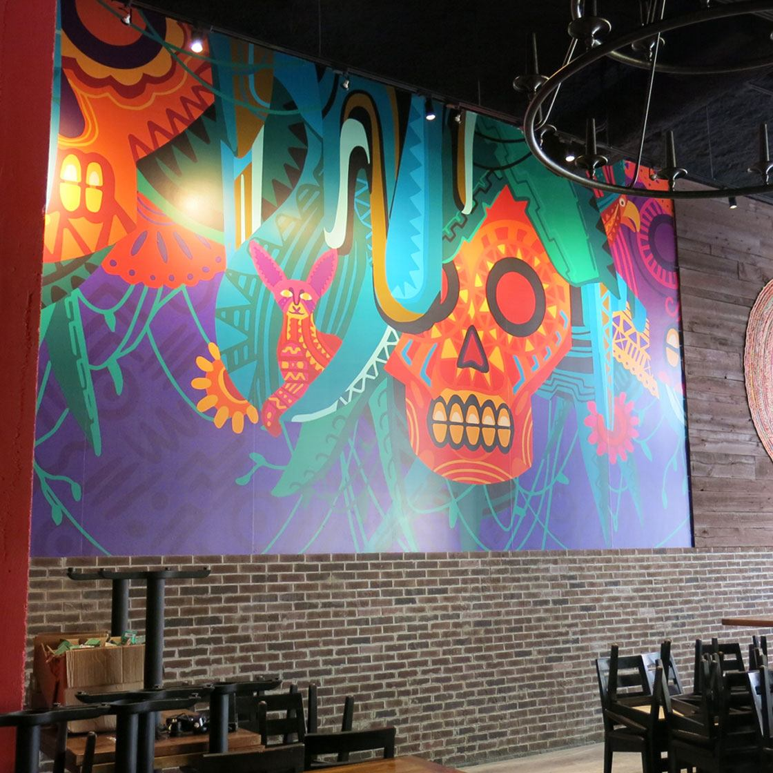 A colorful graphically illustrated mural inspired by Mexican skulls and iconography decorating the seating area of a restaurant