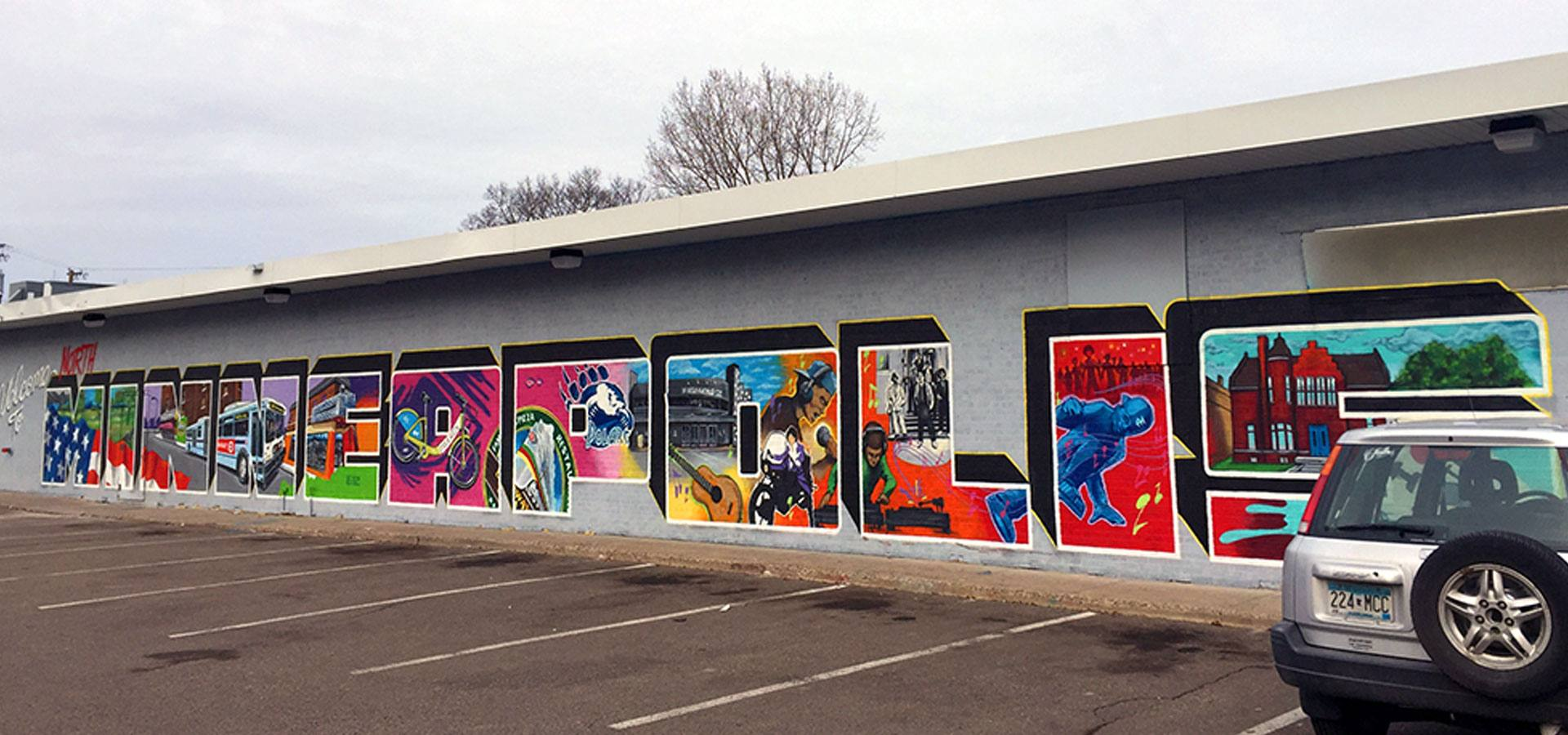 A mural on a parking lot with the words welcome to North Minneapolis decoratively painted