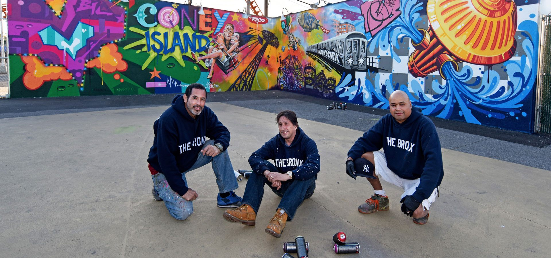 Three people with spray paint cans posing in front of a mural