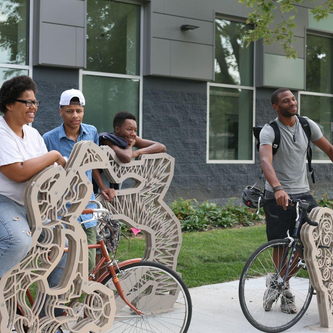 People posing with bike racks in the shape of illustrative break dancers