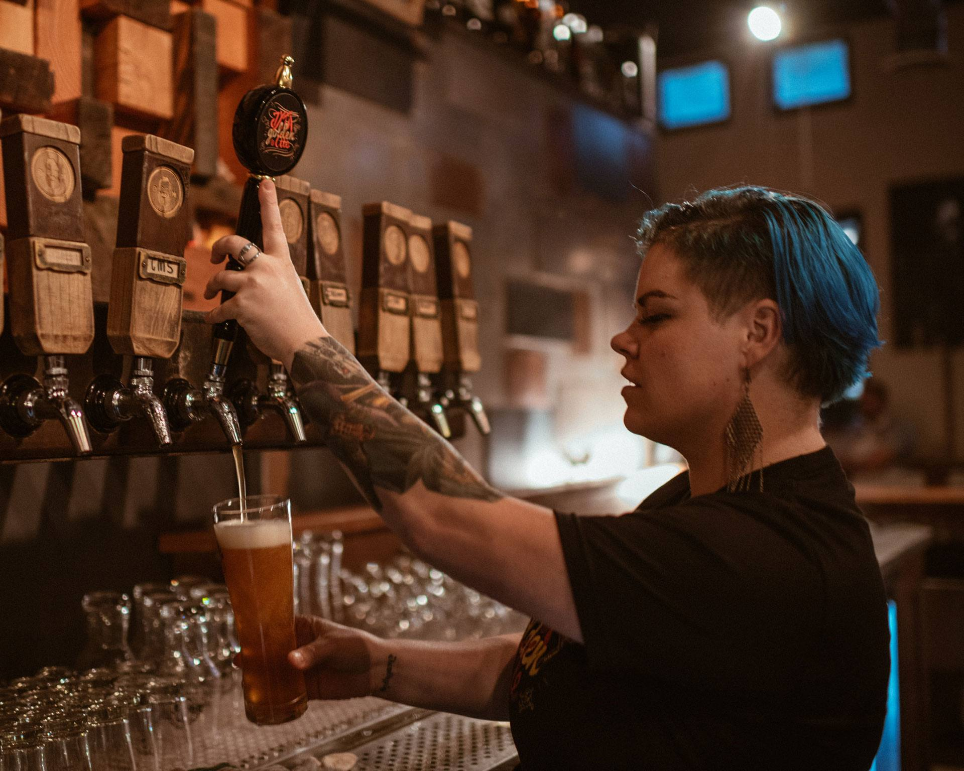 Someone pouring a draft beer