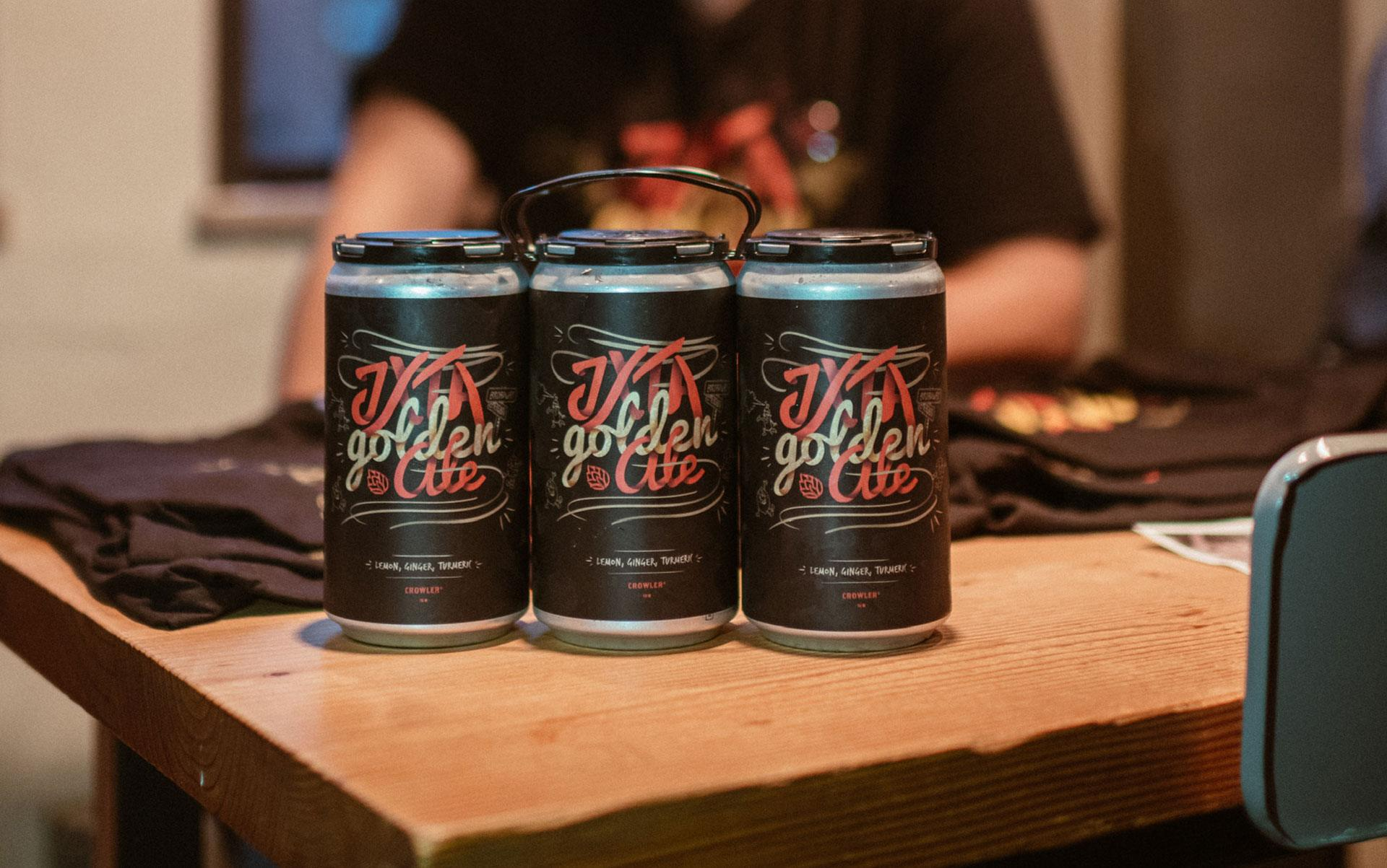 Three drink cans with the same illustrative logo with the words JXTA Golden ale on each