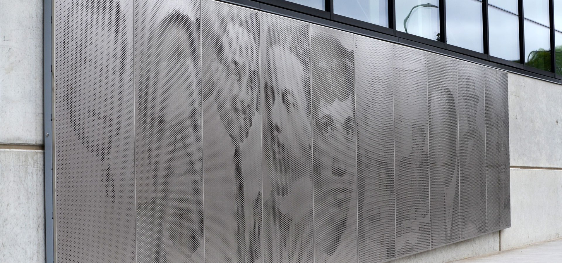 A building wall with decorative portraits etched in metal
