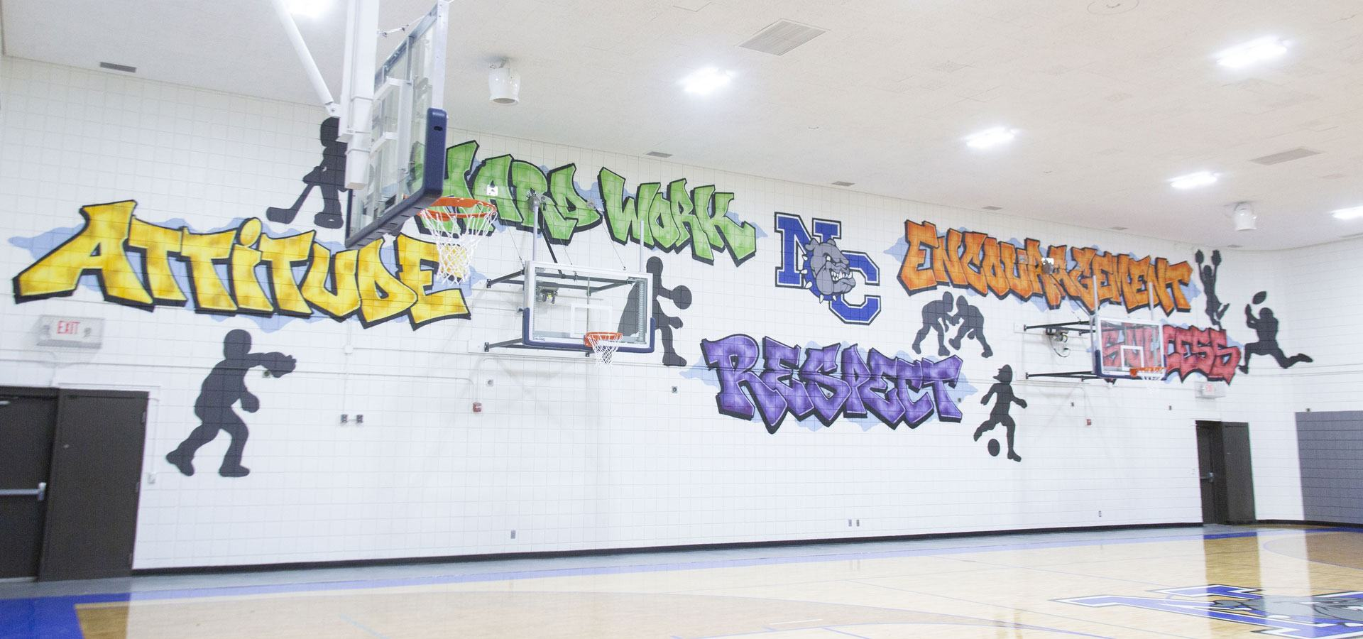 A decorative mural with young people playing sports and the words attitude, hard work, respect, encouragement, success decorating a rec center basketball court