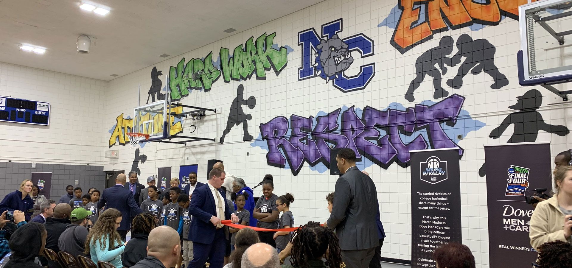 Several people sitting and standing around a ribon-cutting. A celebration of a new decorative mural with young people playing sports and the words attitude, hard work, respect, encouragement, success decorating a rec center basketball court