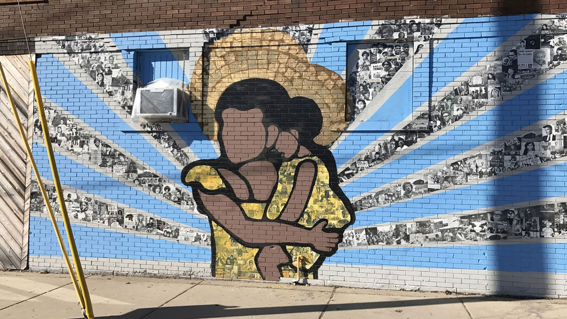 A mural of a faceless brown woman holding a small child with rays of blue and photo collages radiating from them