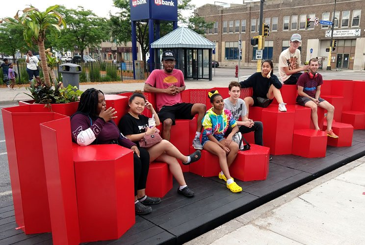 A group of people sitting on a red modular seating area