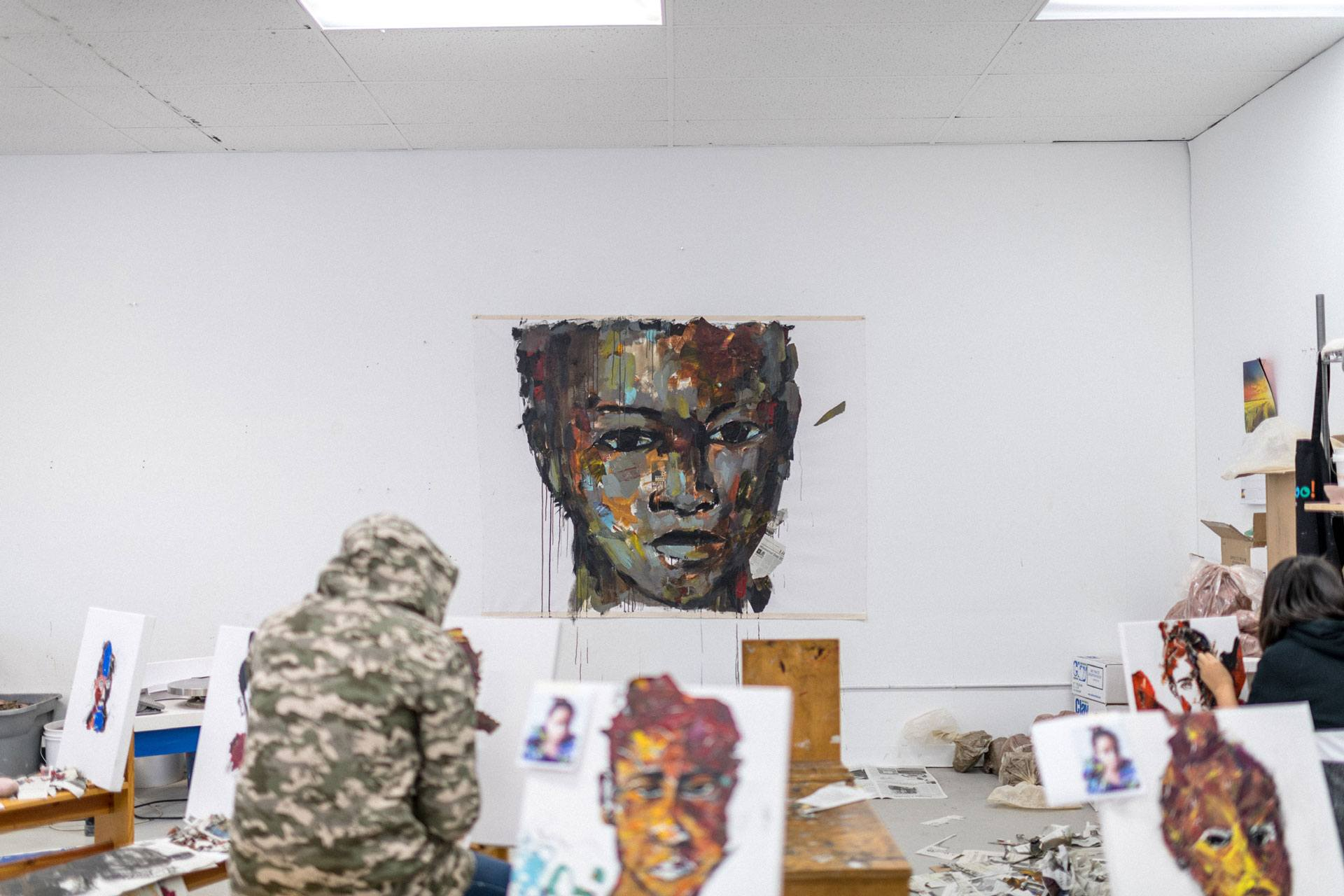 A large multimedia portrait painting in progress displayed in front of an art class