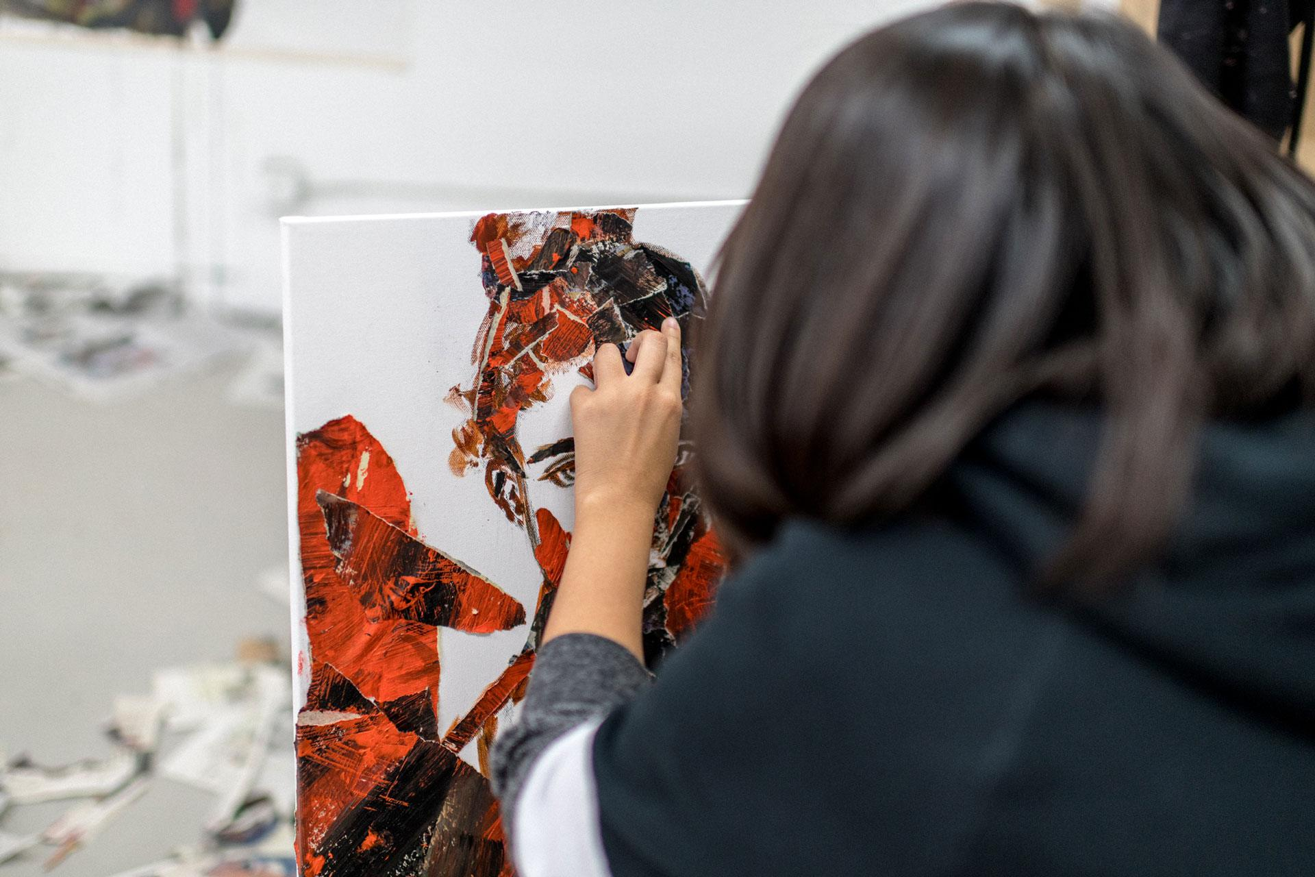 Someone working on a multimedia portrait artwork