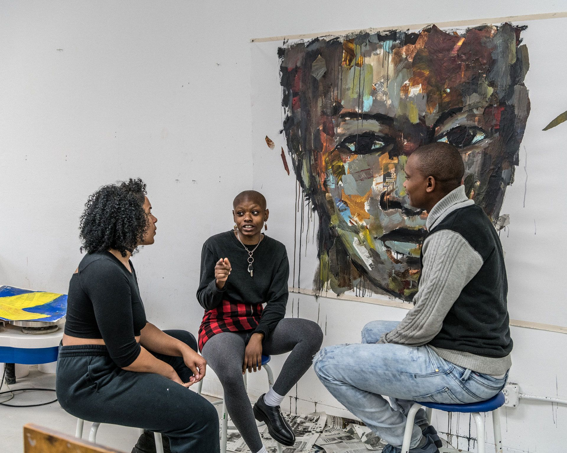 3 people sitting and having a conversation in front of a large portrait painting