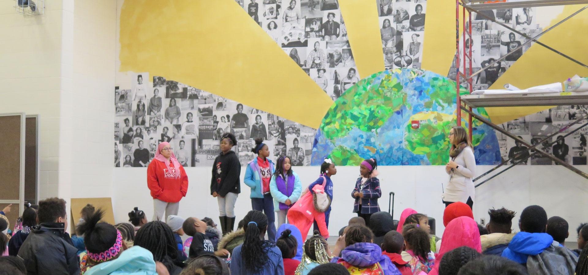 Young people celebrating a collaged multimedia mural of an earth radiating rays and portraits of young people from the school