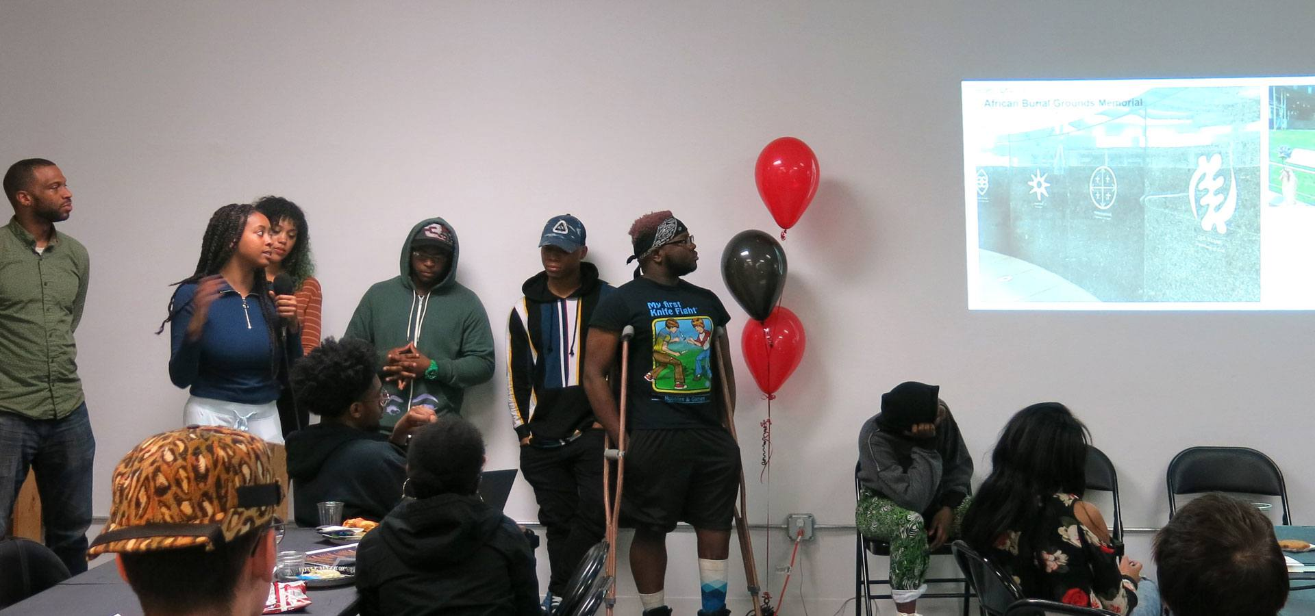 Several young people giving a presentation about a trip to new york city