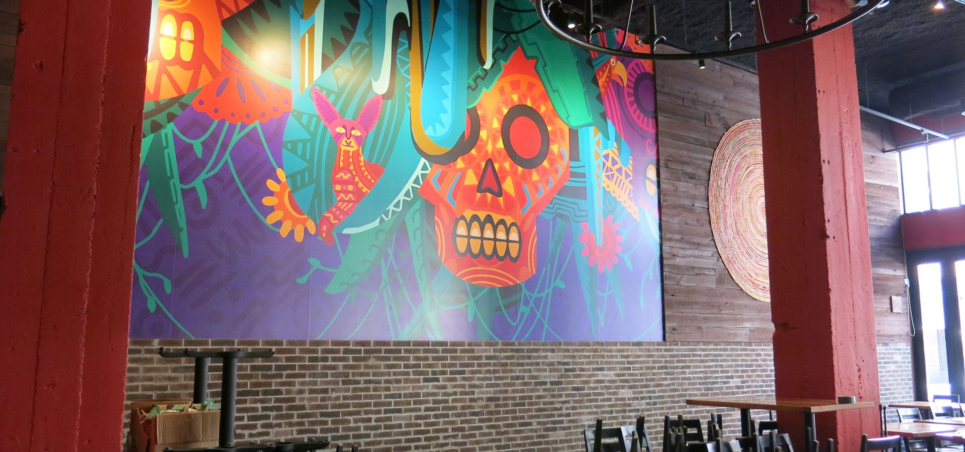 A decorative illustrated mural of a Mexican inspired skull and animals in a restaurant seating area