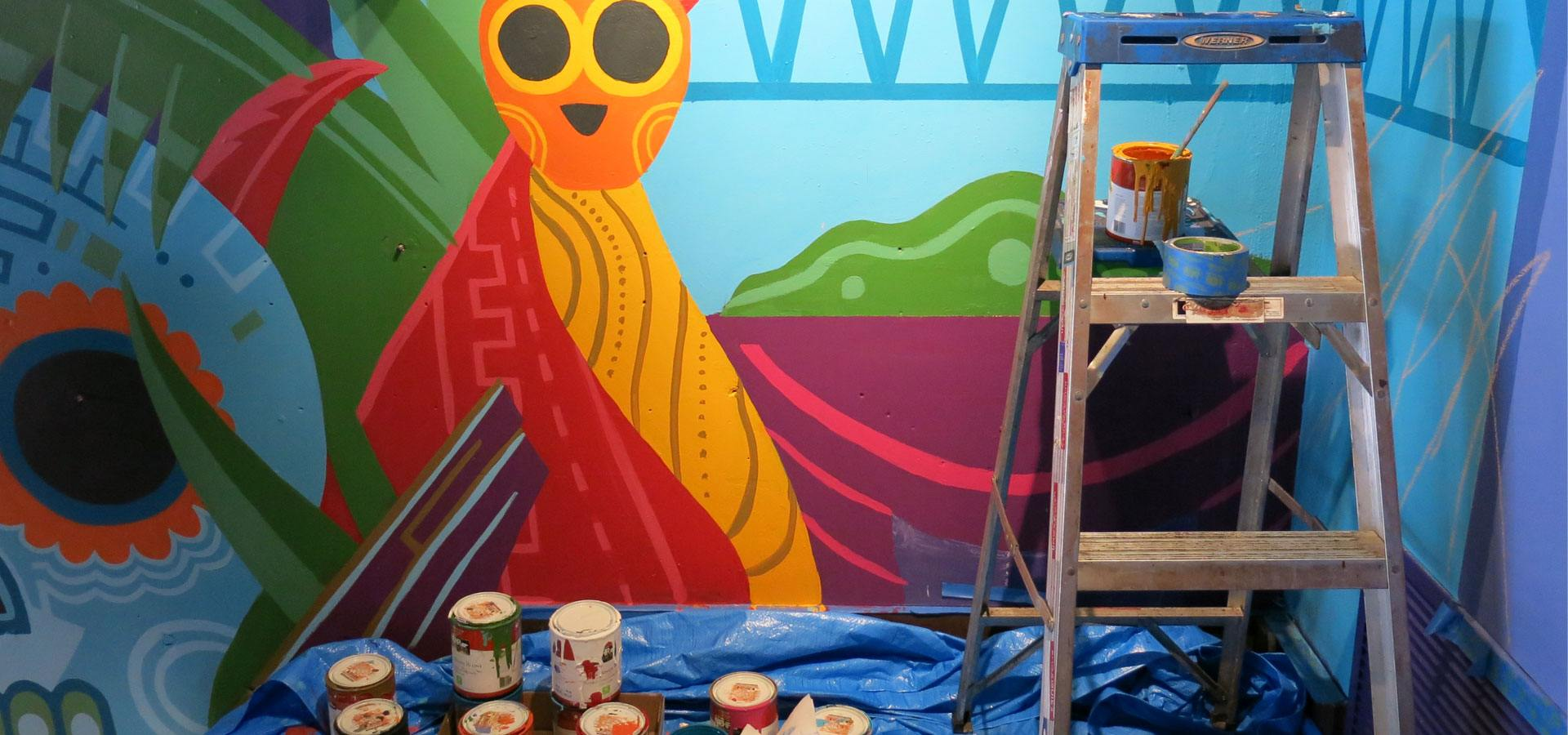A decorative mural inspired by Mexican iconography in progress
