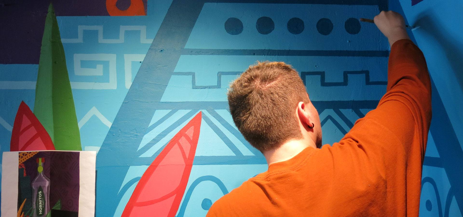 Someone working on a decorative mural inspired by Mexican iconography