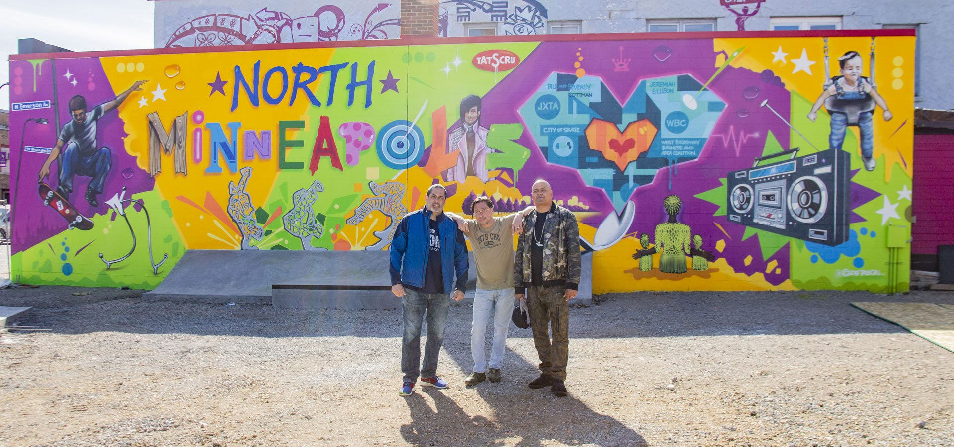 Three people standing in front of a colorful mural with several images and the words North Minneapolis