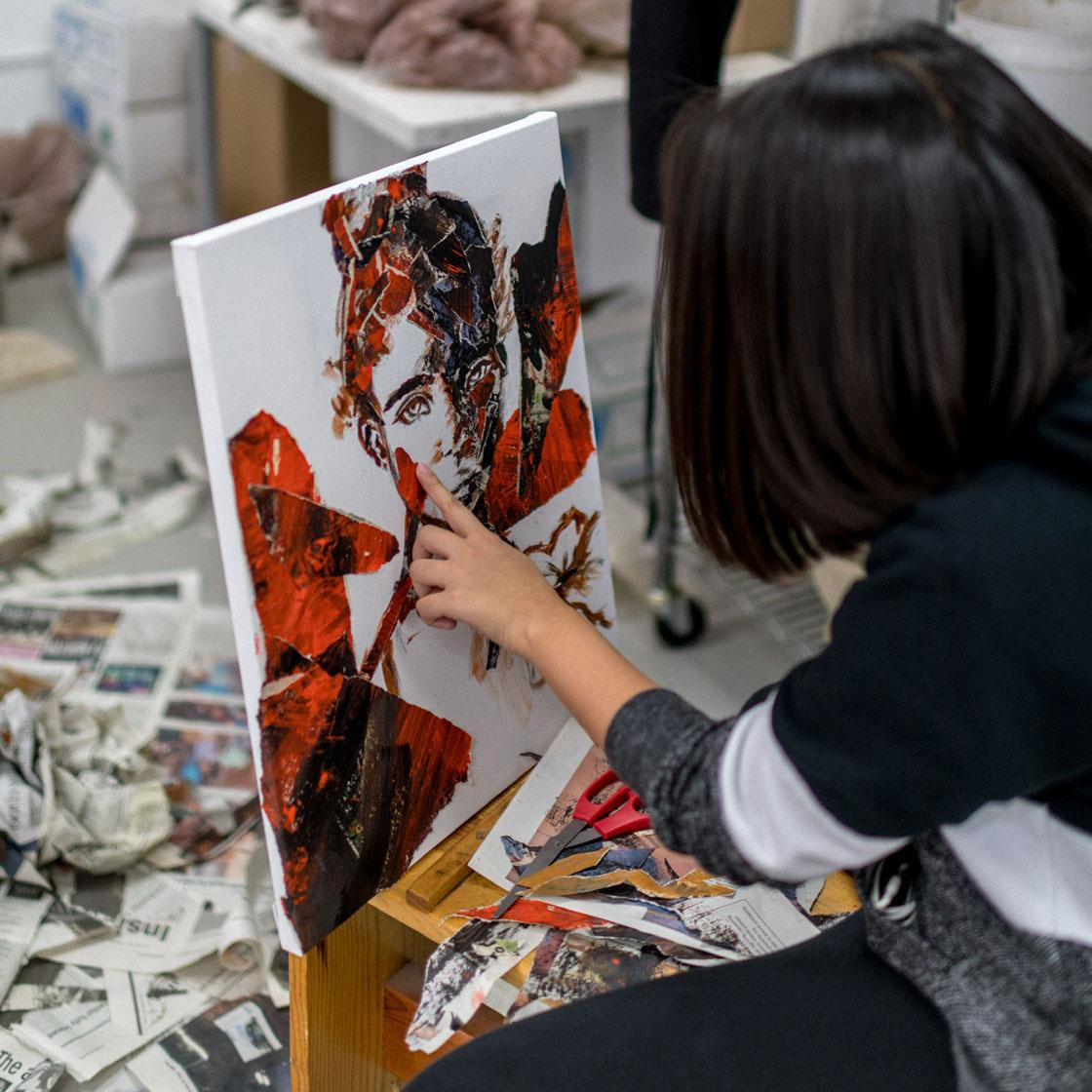 A young person working on a collage portrait art piece