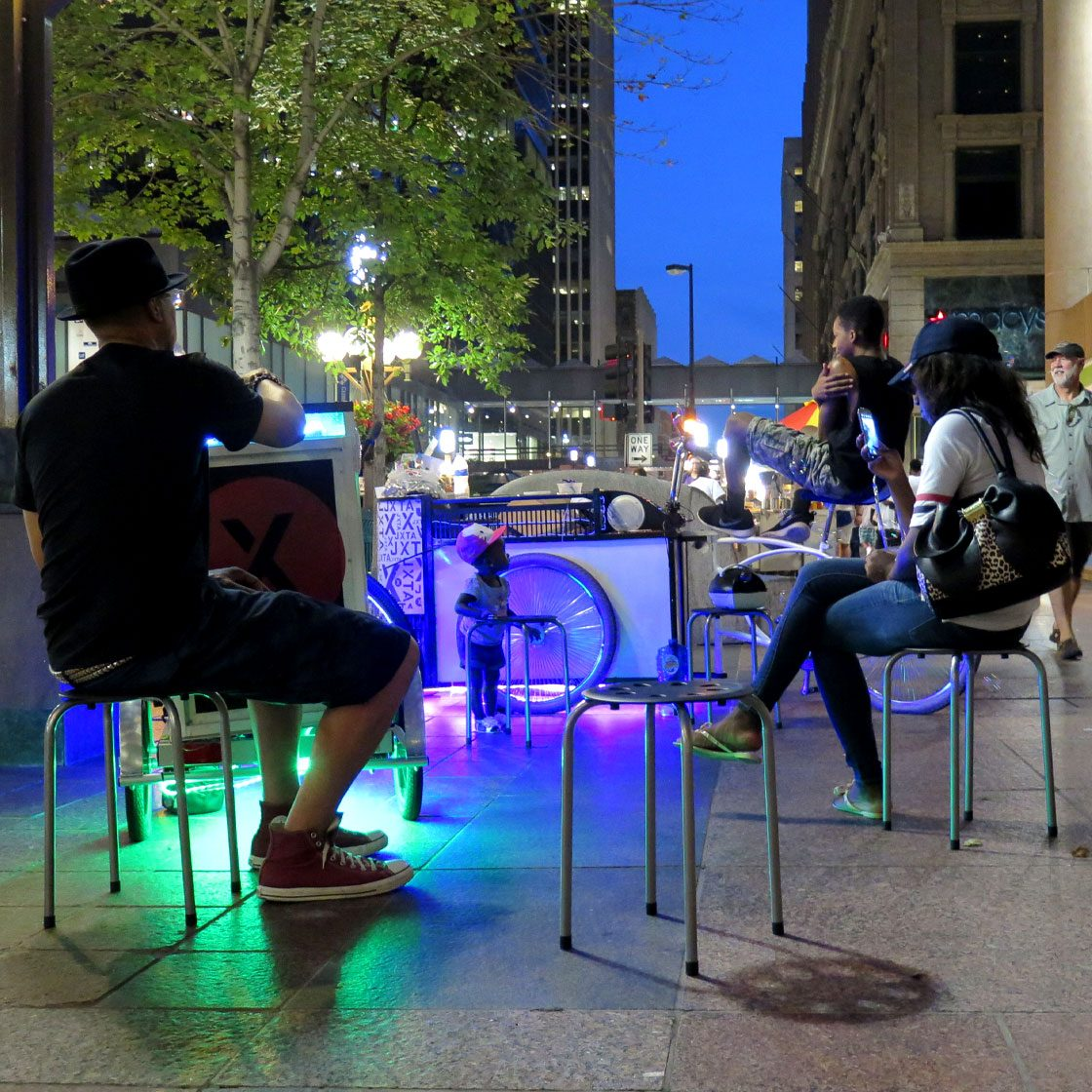 Several people sitting around lit up tables in the dusk on a street