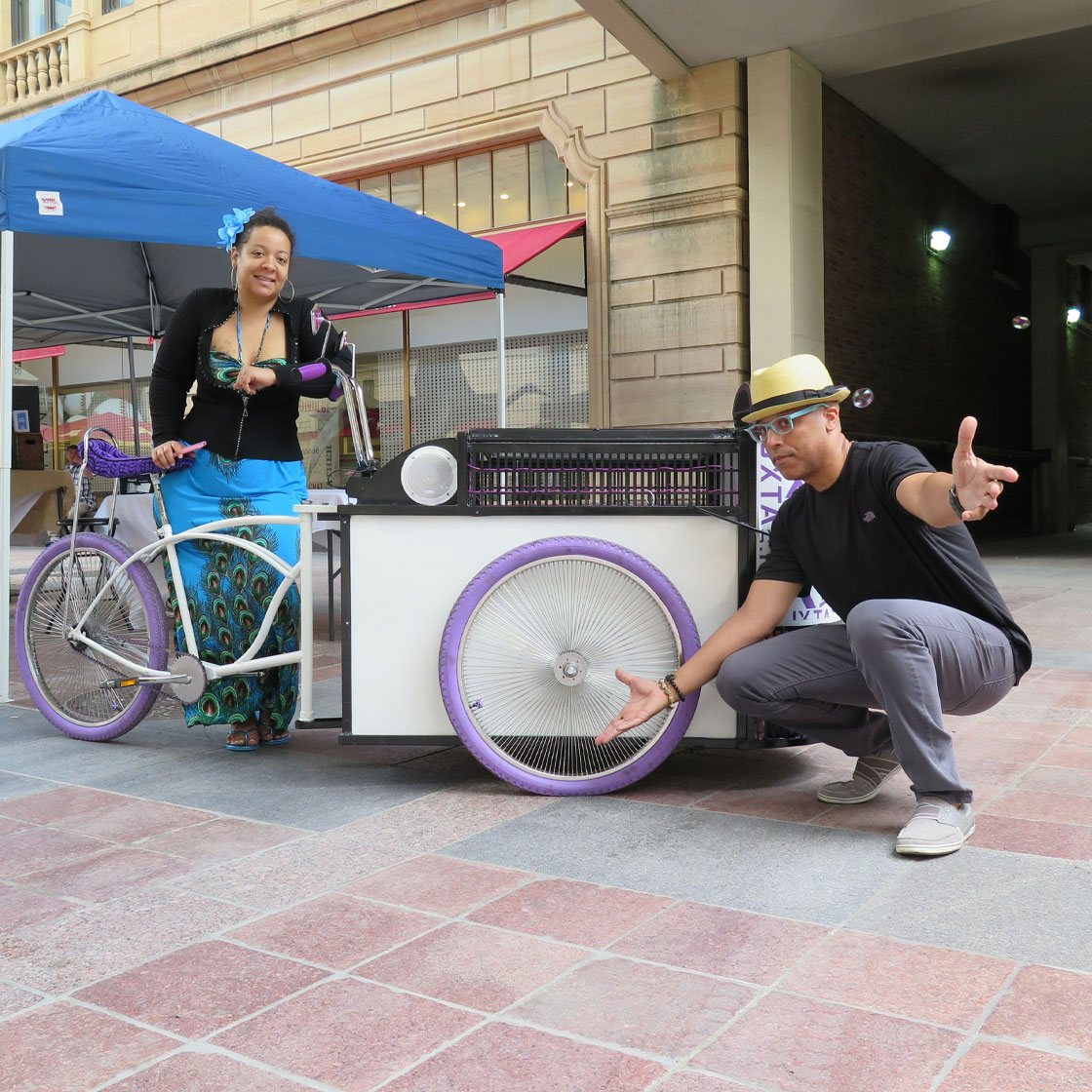 Two people standing around a mobile art unit