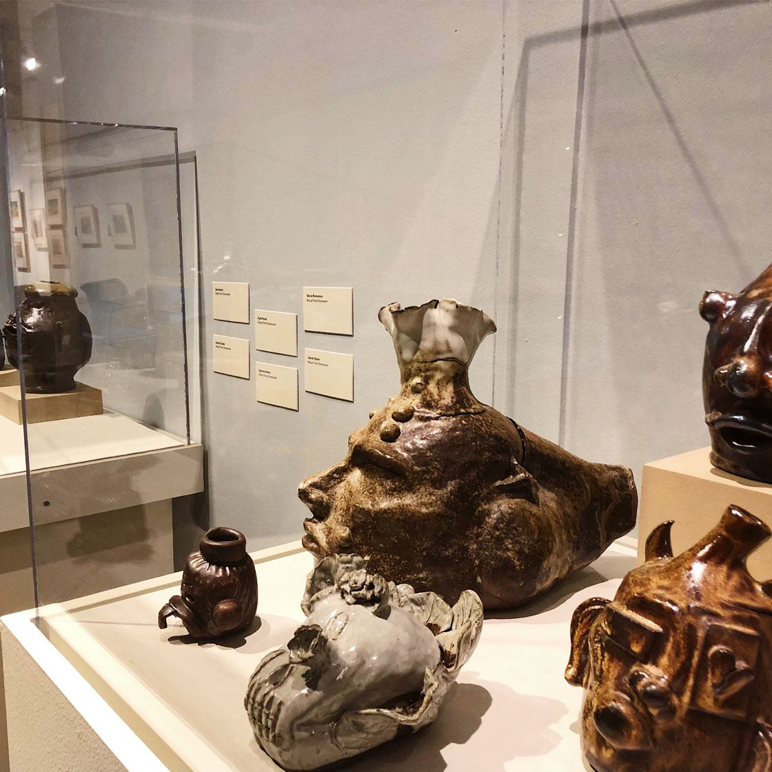 Handcrafted ceramic works in various abstract face shapes displayed in museum display cases