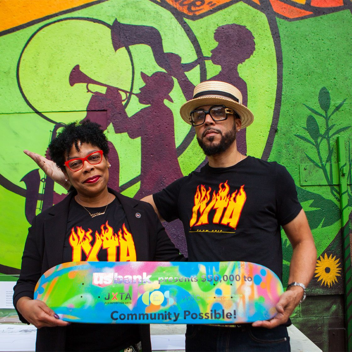 Two people holding a skate deck