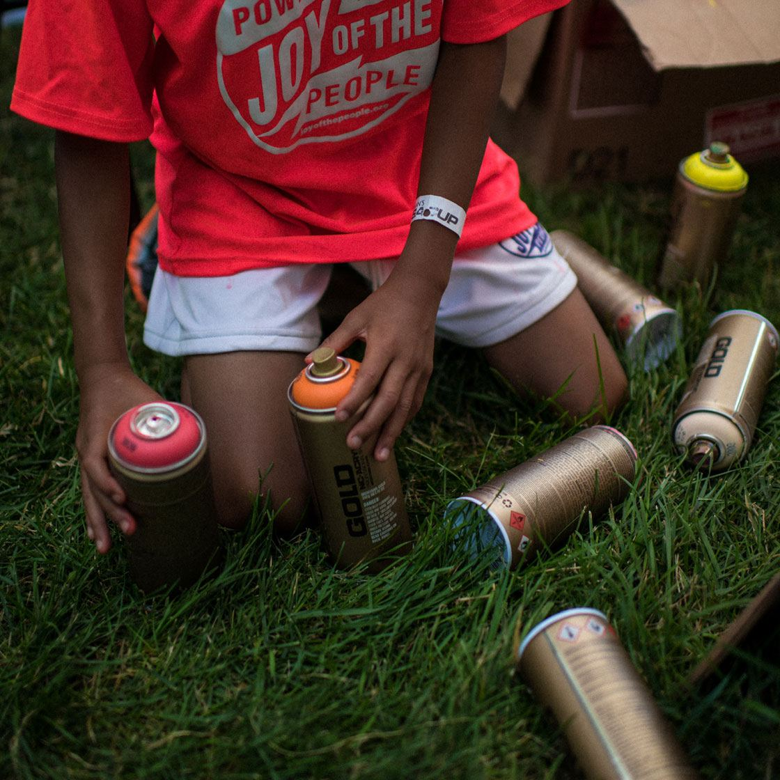 A young person handling several paint cans in different colors