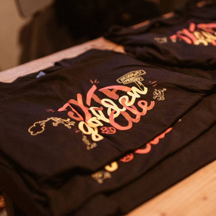A stack of screen printed t shirts with the words JXTA Golden Ale in a calligraphic style illustration