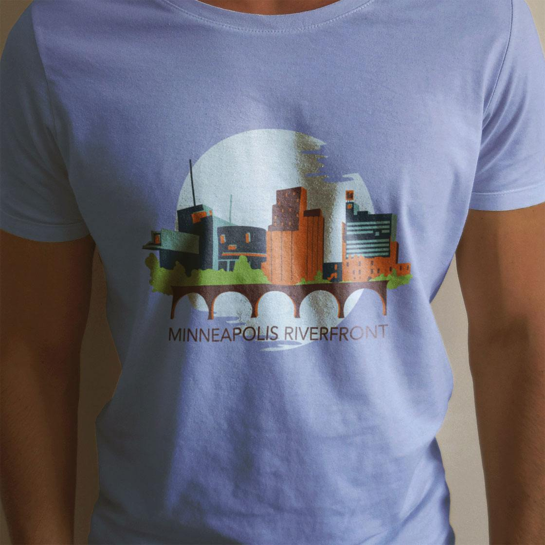 Someone modeling a t shirt with an illustration of a skyline with the words minneapolis riverfront