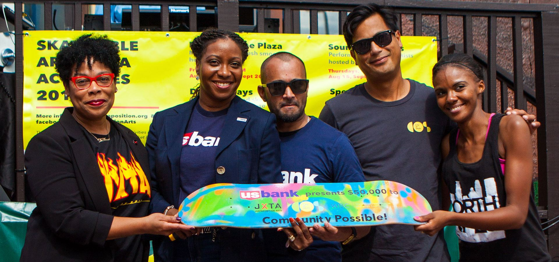 Several people posing with a commemorative skateboard with the words US Bank presents $50,000 to JXTA, City of Skate, and West Broadway Coalition for Community Possible!