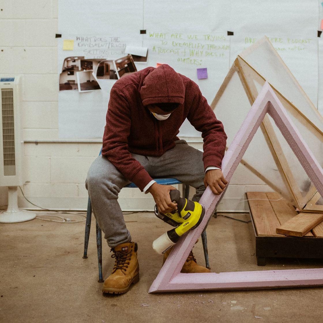 Someone working on a styrofoam pyramidal shaped sculpture
