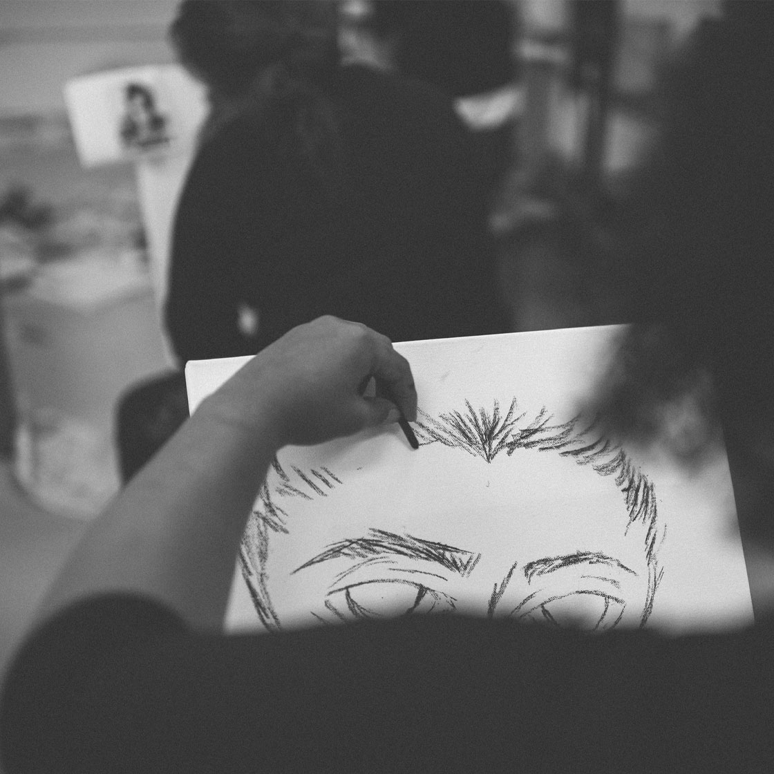 Someone starting a drawing of a charcoal portrait