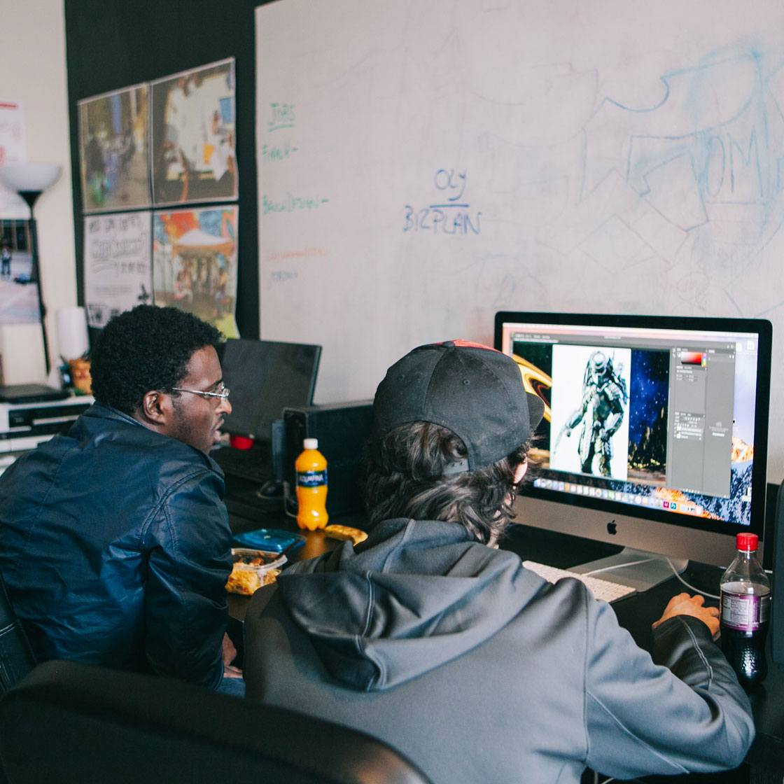 Two people sitting in front of a computer working on an illustration