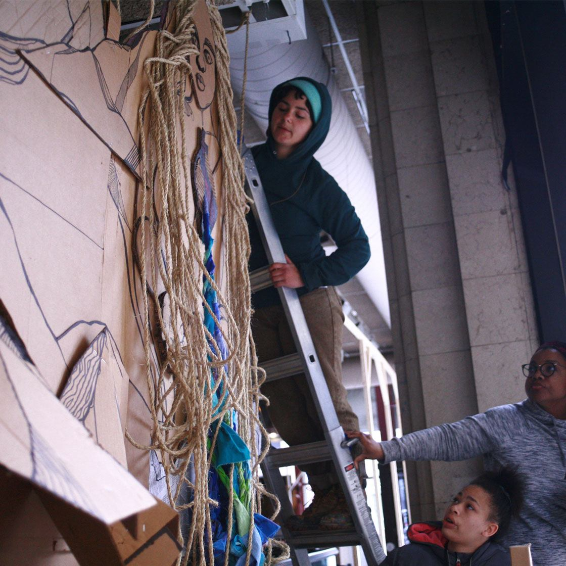 Several people working together to hang an art installation