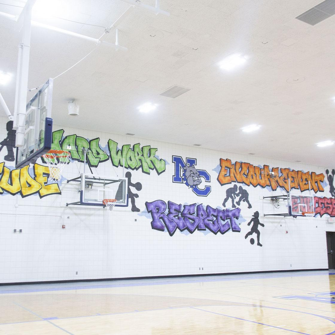 A gymnasium basketball court with a painted wall mural with the words Attitude, Hard Work, Respect, Encouragement, Success