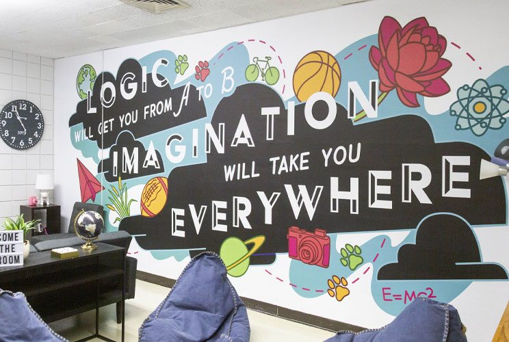 A lounge area with a wall mural designed with the quote Logic will take you from A to B, Imagination will take you everywhere